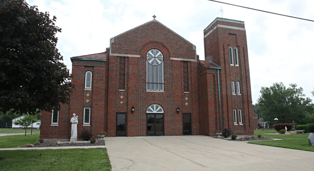 Red brick Church with stained glass windows, cement cross on top, white statue, wide sidewalk in front.