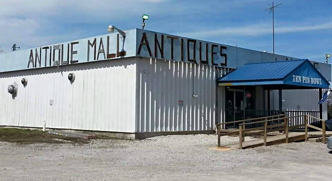 Cream sided building with Antique Mall Antiques with gravel parking area, wood ramp with railings at entrance.