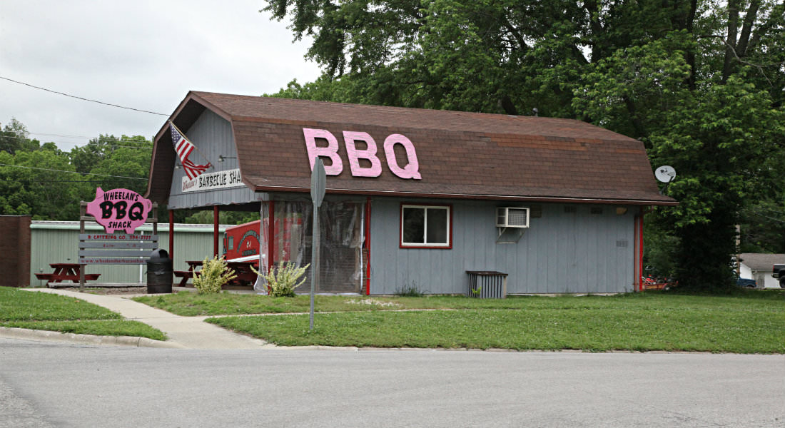 Grey building with brown roof that looks like barn, Pink pig shaped Sign Wheelan's BBQ Shack