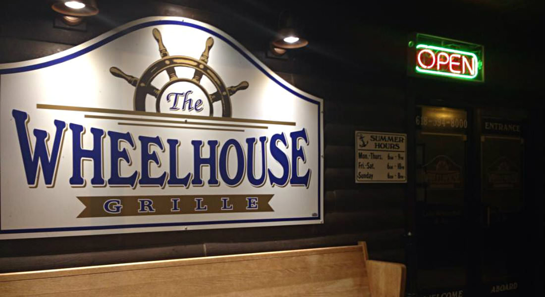 Cream sign with blue lettering The Wheelhouse Grille lit up at night, boat wheel on sign at top.