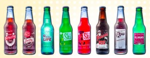Variety of glass soda bottles with caps and labels offered by Excel Brewing Company.