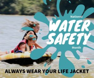 Copy of a water safety poster showing two girls in a raft being pulled behind a motor boat. Both are wearing life jackets.